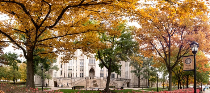 A Cathedral of Learning entrance with autumnal trees in the foreground