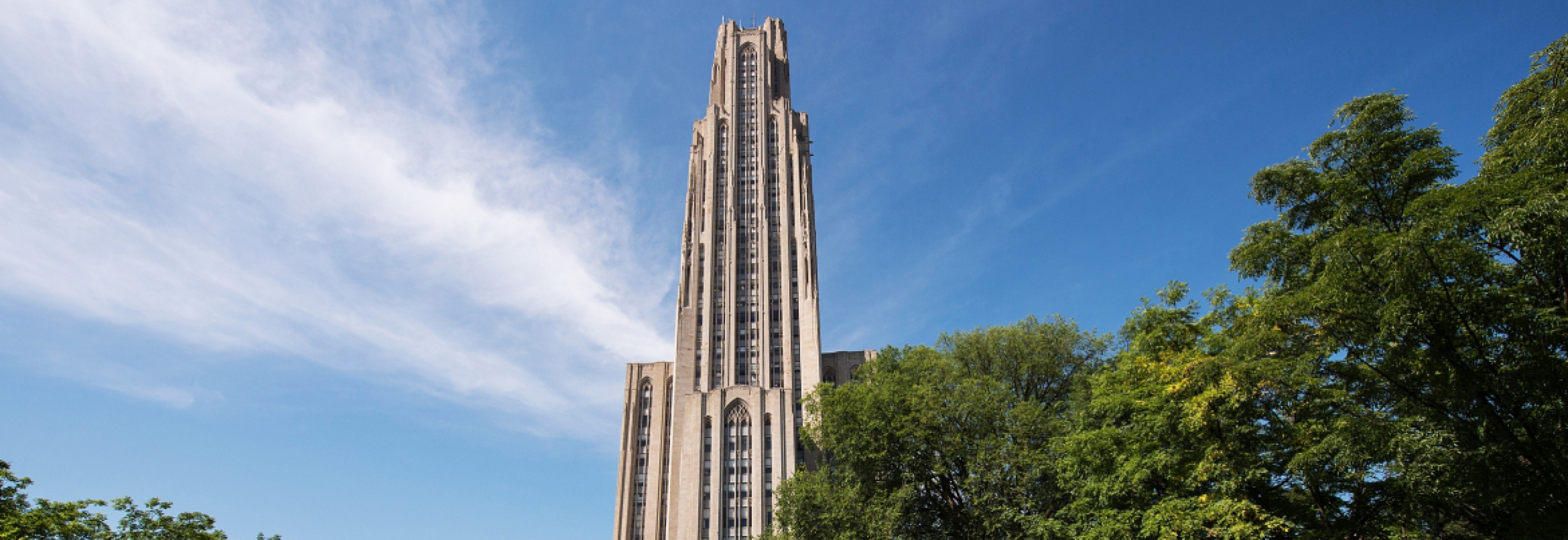 Cathedral of learning surrounded by clouds and trees